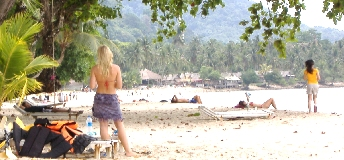Blond girl in miniskirt on lonely beach